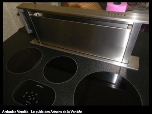 Cuisine avec ilôt. Les plaques de cuisson sont parfaitement intégrées dans le plan de travail en granit. La hotte ilôt sort du plan de travail pour fonctionner et faire office de crédence. 85 - La Tranche sur Mer