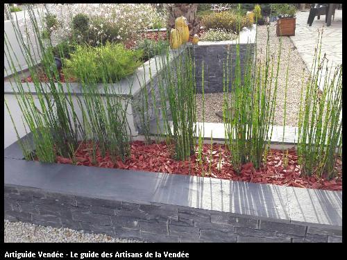 Pose de parements déco et margelle, copeaux rouge, installation de plantes style equisetum pour jardinières réalisation Pépinières Grelier