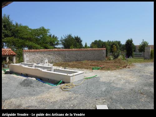 Aménagement d'une cour : bassins en cascade, mur de moellons en arc de cercle, réseaux enterrés et pose de pavés. Saint Pierre le Vieux Vendée 85