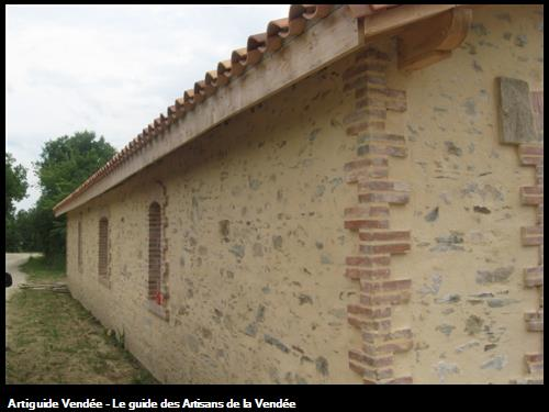 Enduit à pierres vues et pose de briques sur angles et entourage des ouvertures.