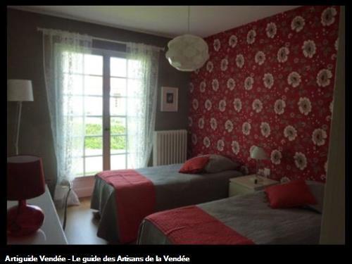 Chambre : Tapisserie fleurie sur tête de lit et tapisserie unie sur 3 murs, dans la commune de la Ferrière 85280