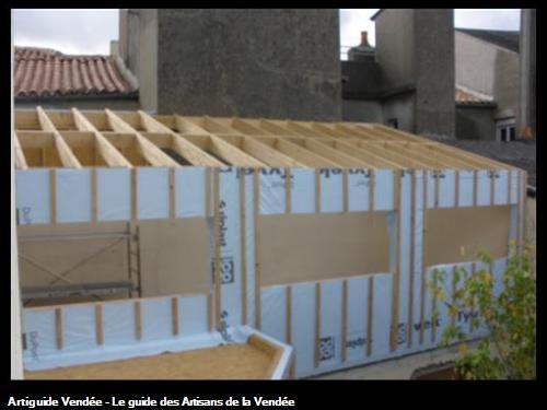 Extension ossature bois avec toit terrasse et charpente traditionnelle en cours d'éxécution